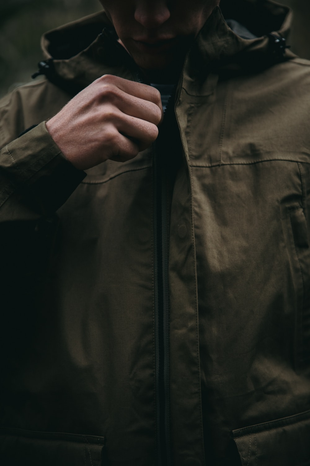 person zipping up brown hoodie