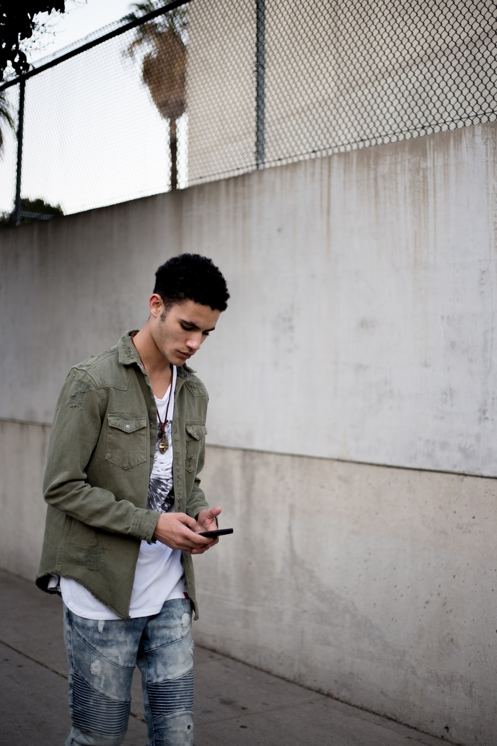 man looking down while holding phone near wall