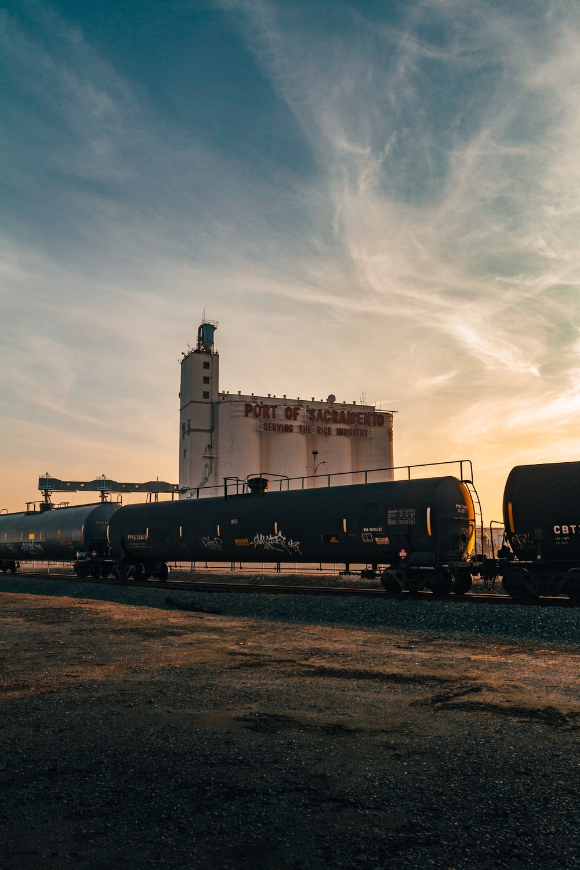 tanker train near port building under white sky