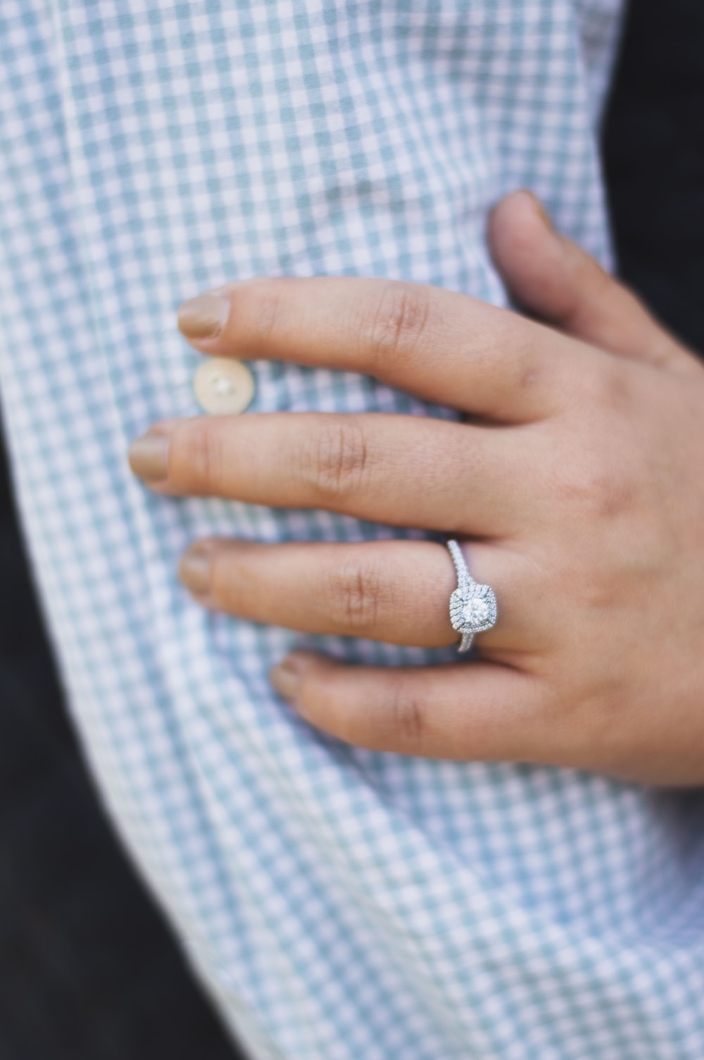 person wearing silver-colored ring with clear gemstones