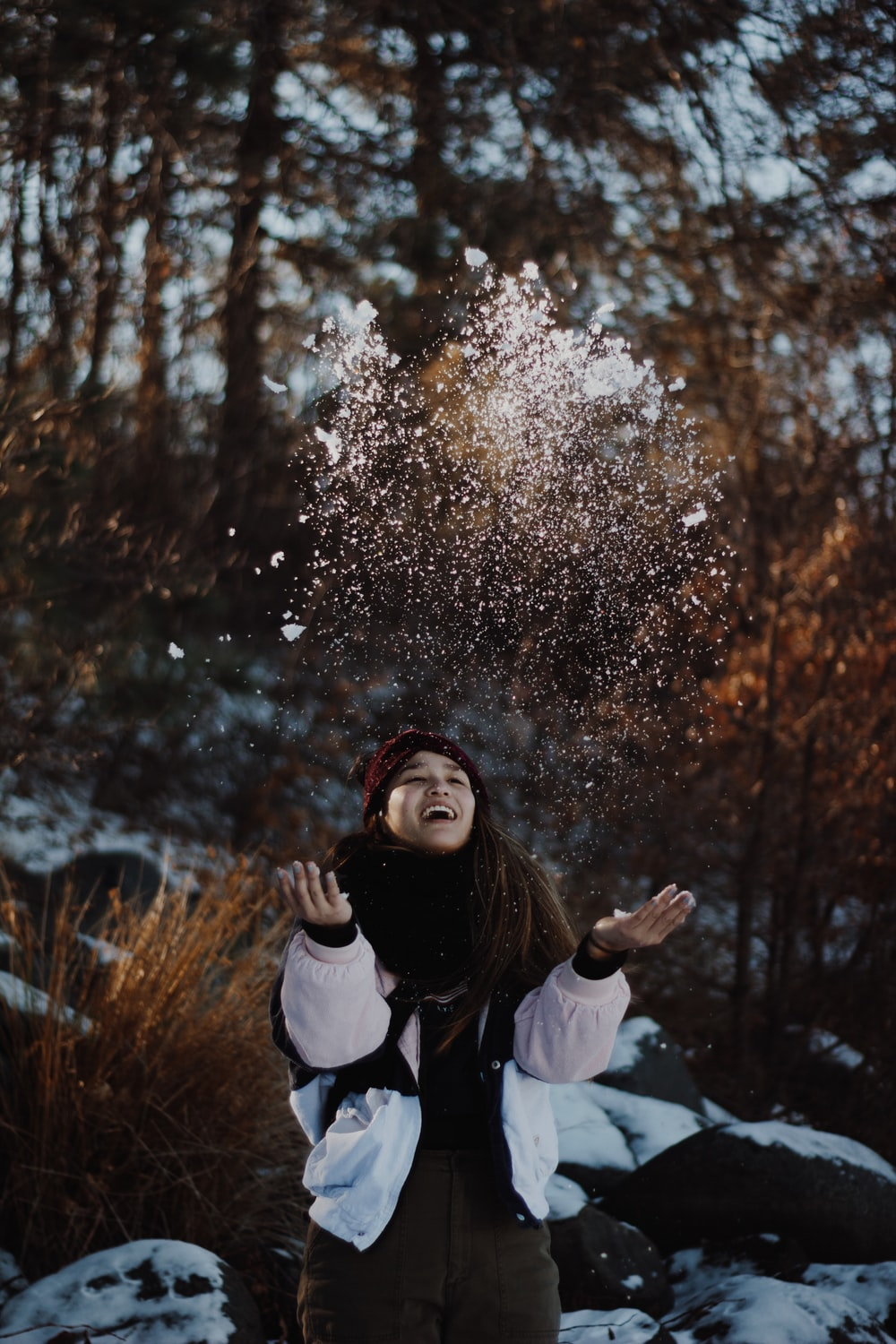 smiling woman throwing snows up in the air near woods during daytime
