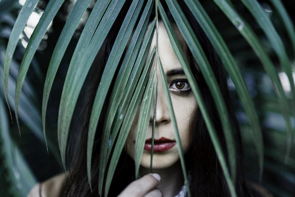 woman hiding on fern leaf