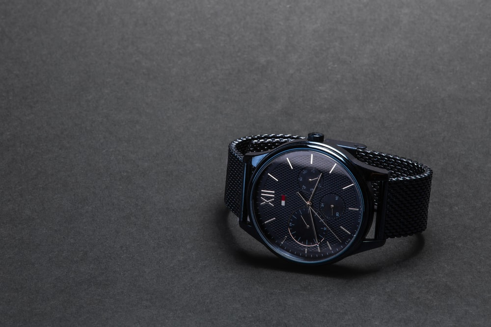 round black Tommy Hilfiger chronograph watch on black surface