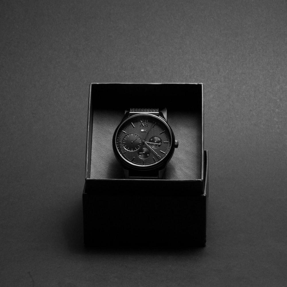 round black chronograph watch in case