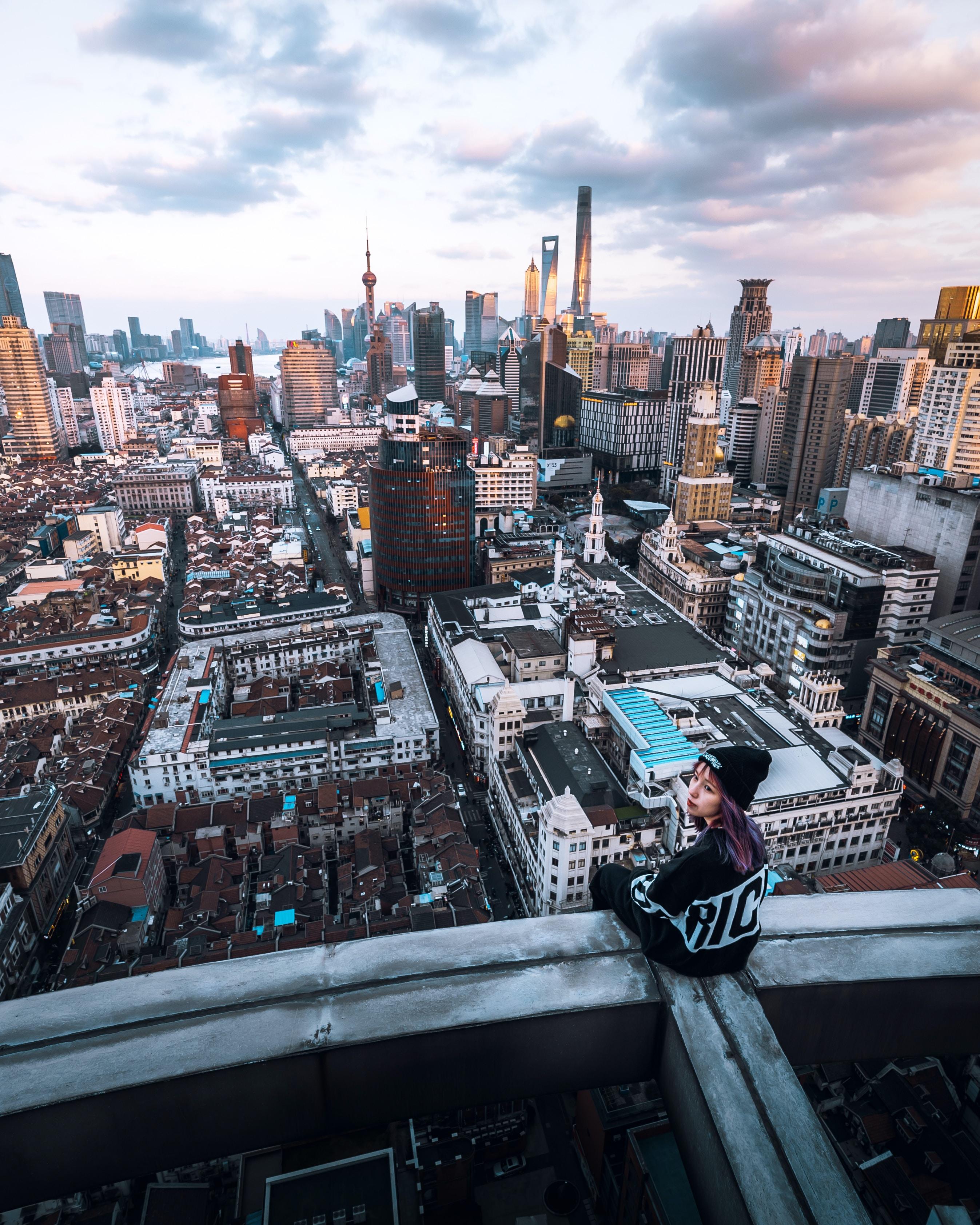 woman sitting on rooftop looking backward overlooking city