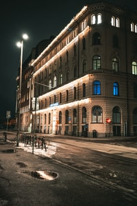 empty street with lighted concrete building during nighttime