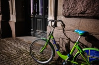 green bicycle leaning on wall