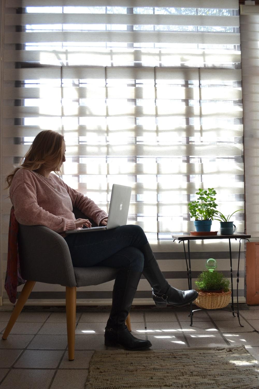 woman sitting on chair near window