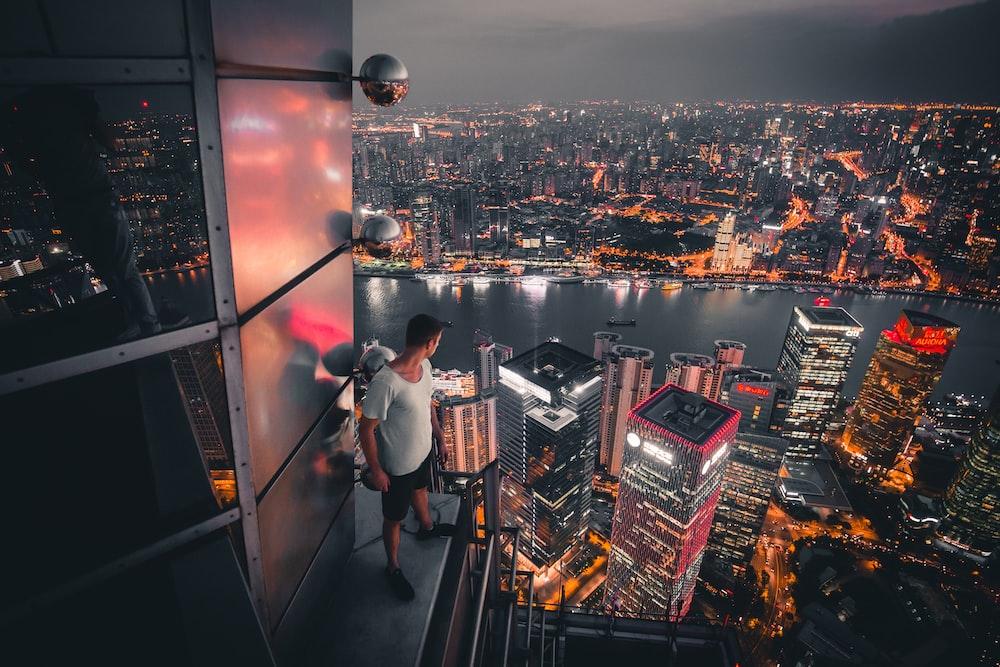 man standing at buildings rooftop overlooking city