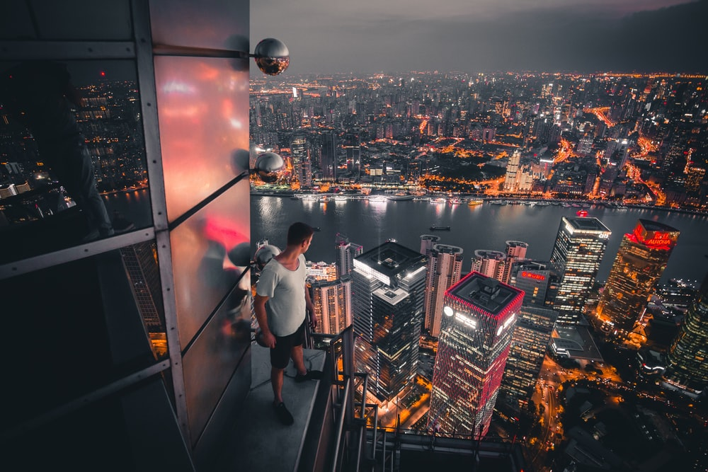 man standing at buildings rooftop overlooking city