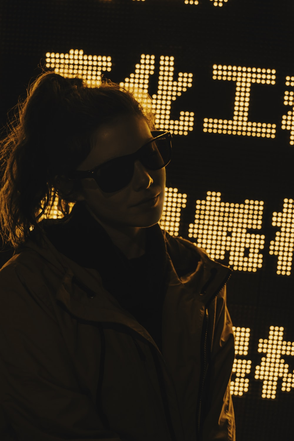 pony-tailed hair of woman in brown jacket wearing black sunglasses