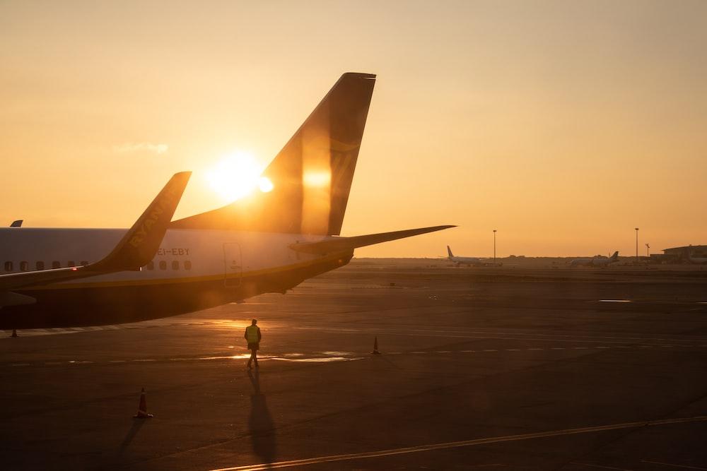 man walking under jet plane at the tarmac during sunset