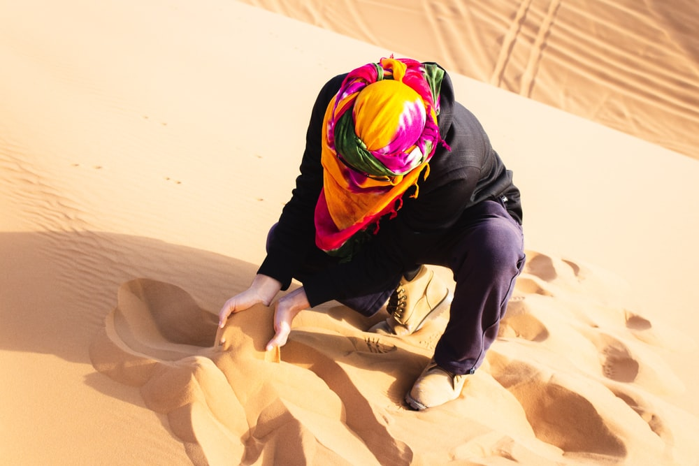 man scooping desert sand with both hands