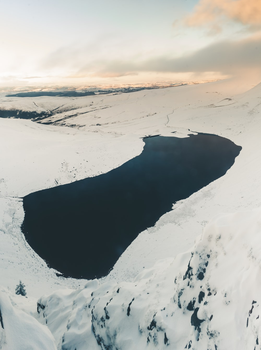 calm body of water surrounded with mountainous terrain covered with snow at daytime