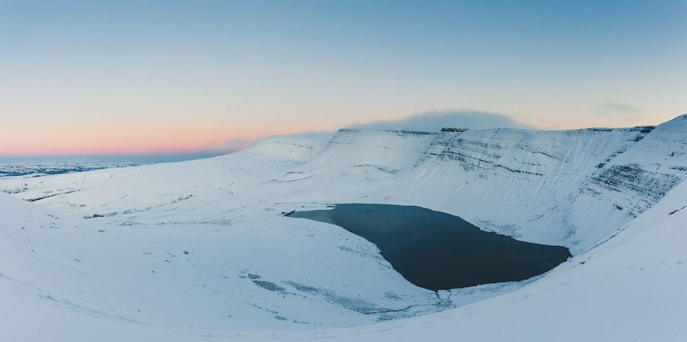 body of water between snow mountain