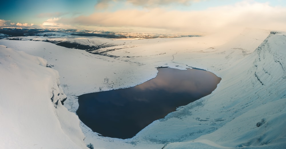 snow covered lake under grey cloudy sky