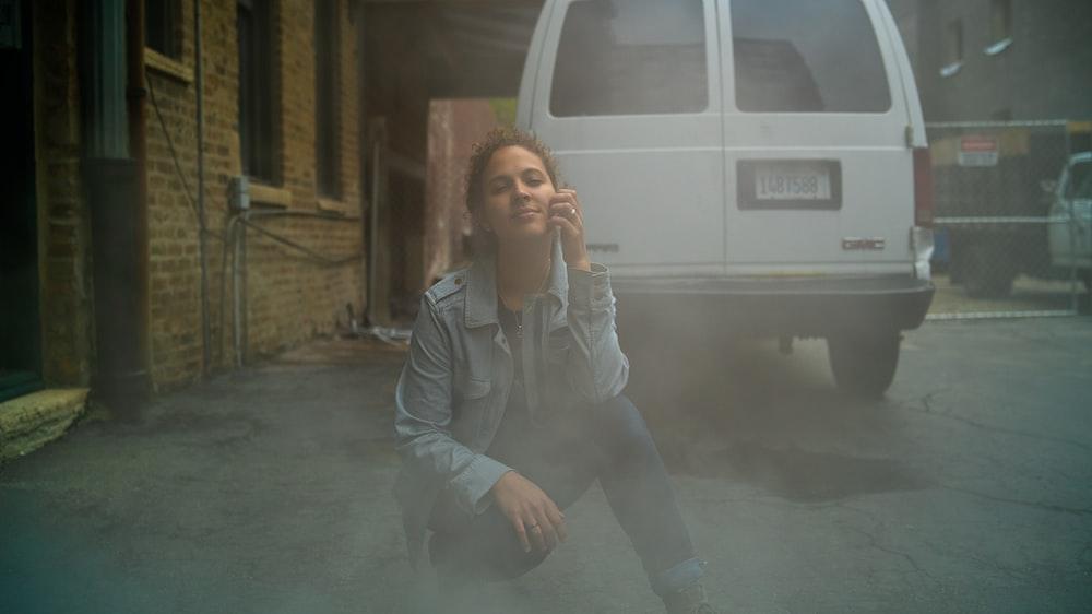 woman kneeling on ground beside car