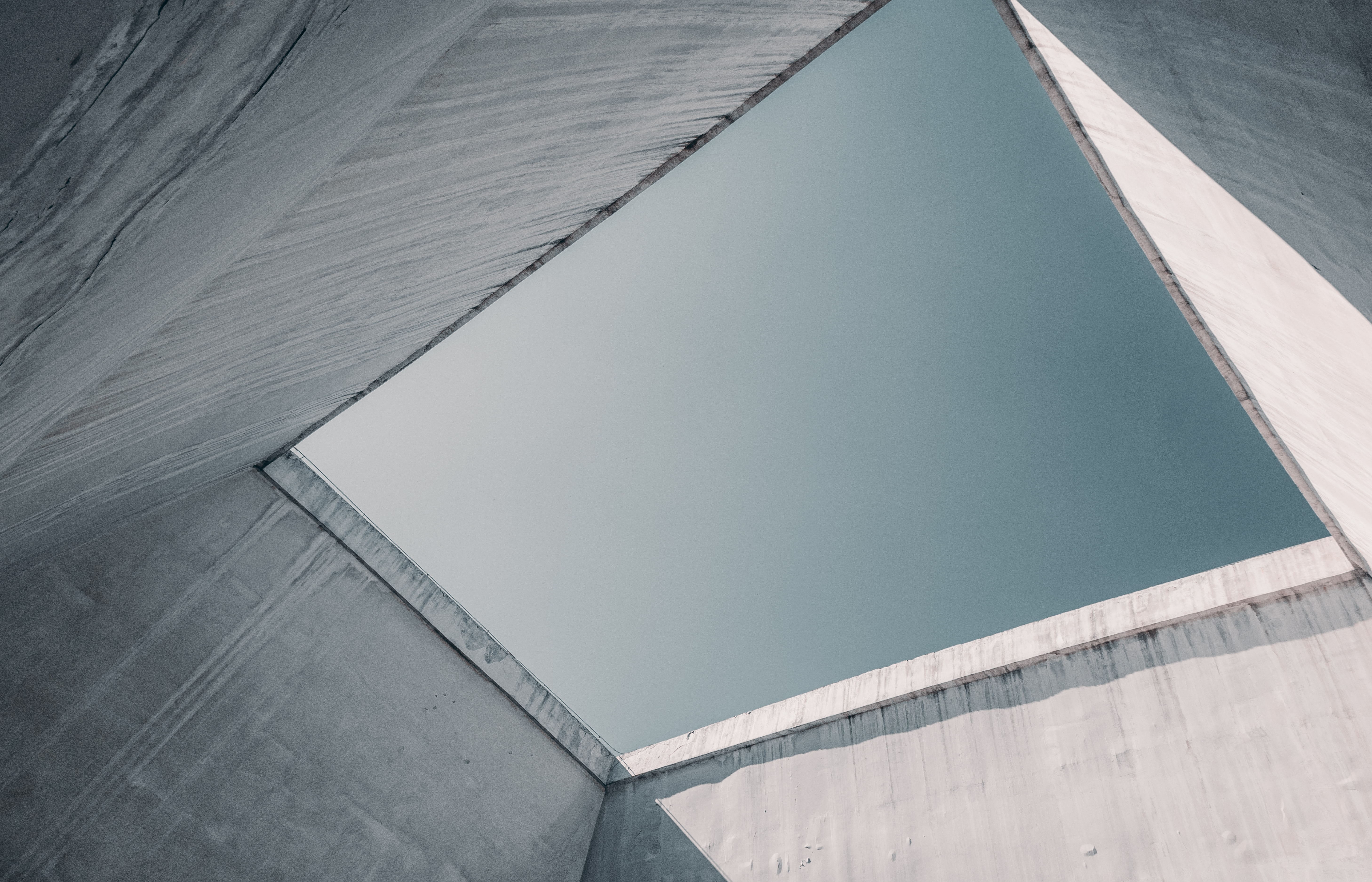 low angle photography of grey concrete walls under white and blue sky
