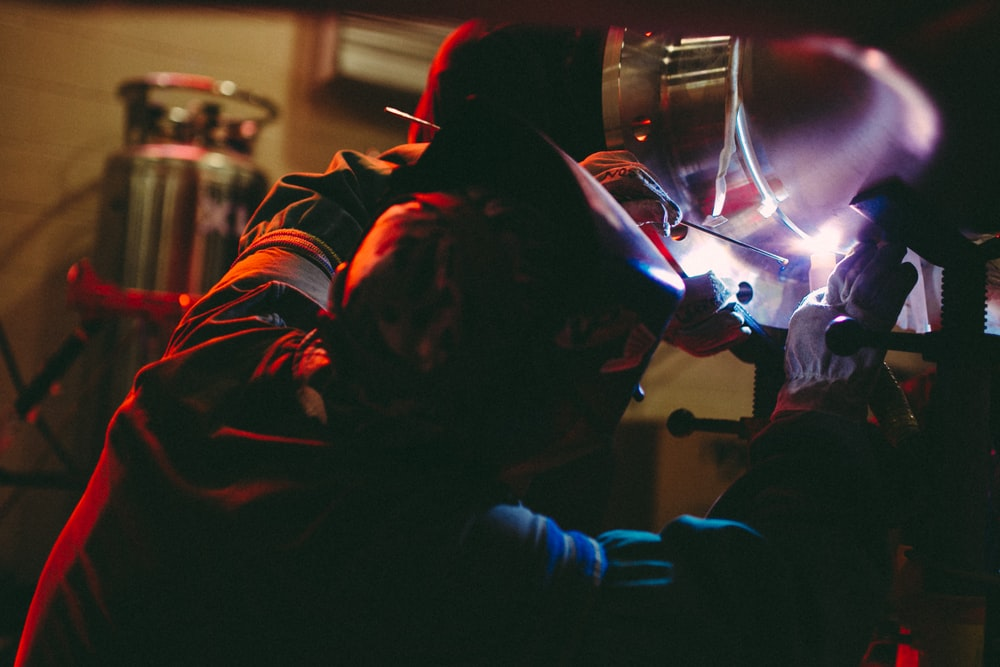 person welding on metal inside lighted building