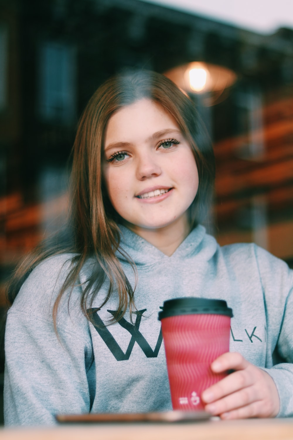 woman in grey pullover hoodie holding red and black disposable cup