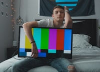 man sitting on bed while carrying flat screen TV