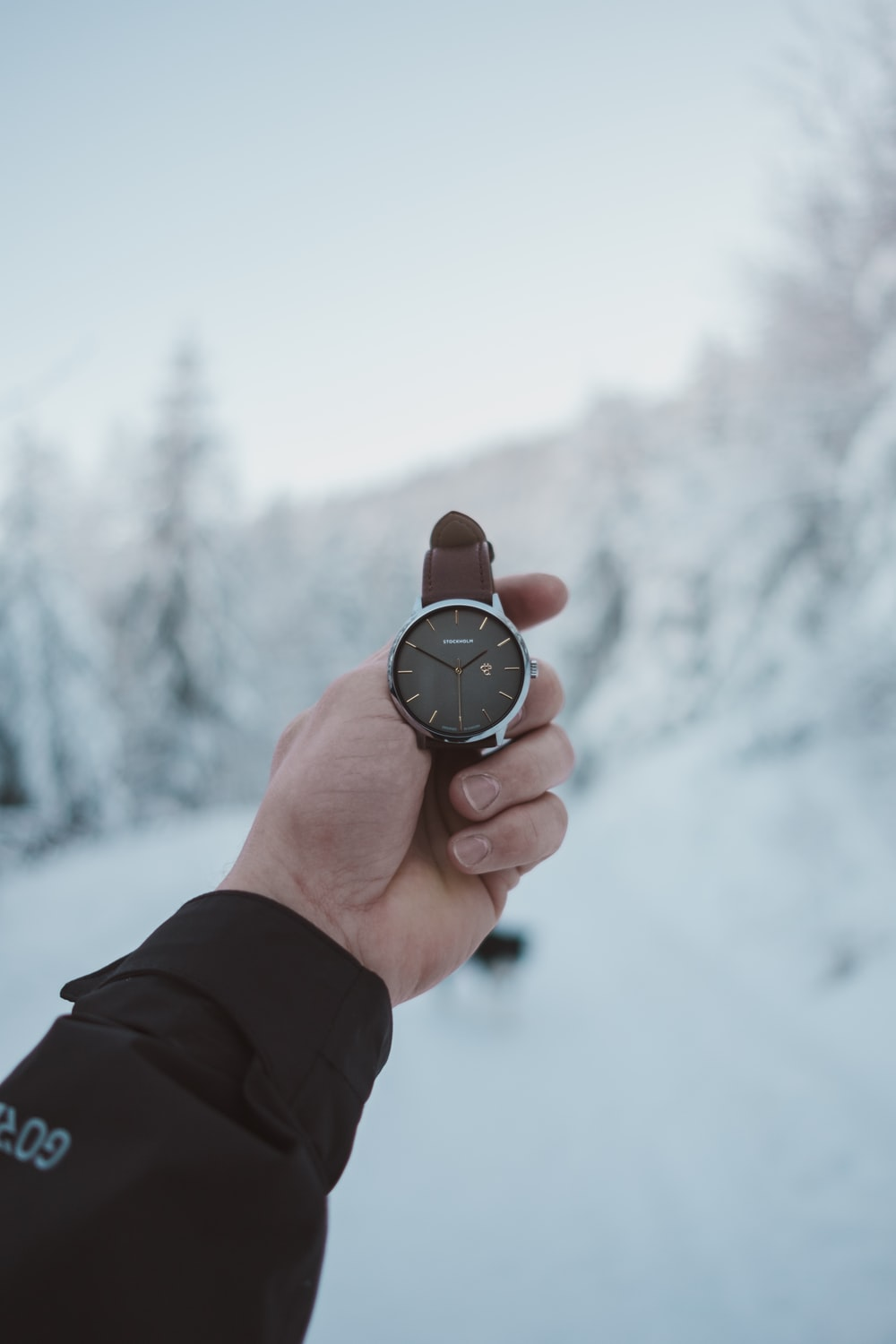 person holding round silver-colored analog watch with brown leather band at 2:50