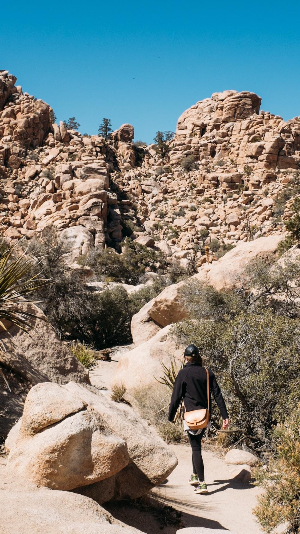 woman walking near rock formation during daytime