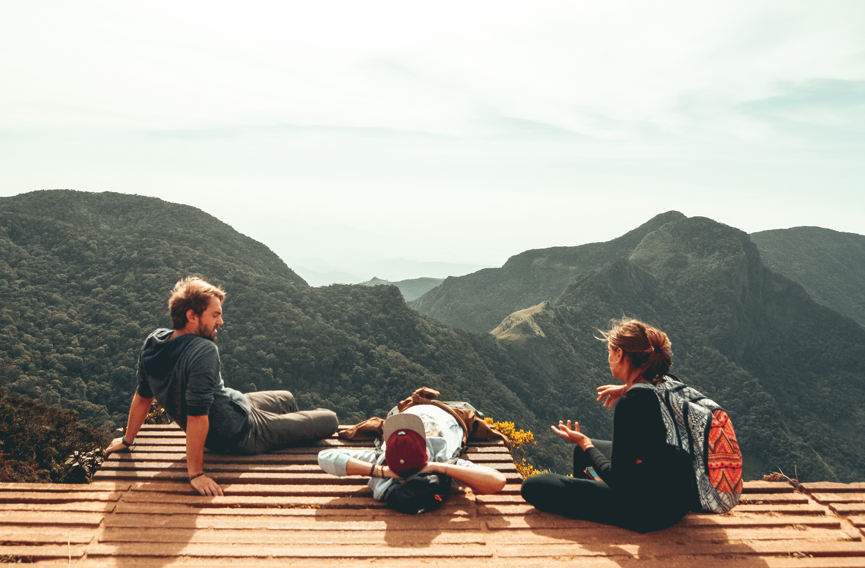 three people overlooking mountains