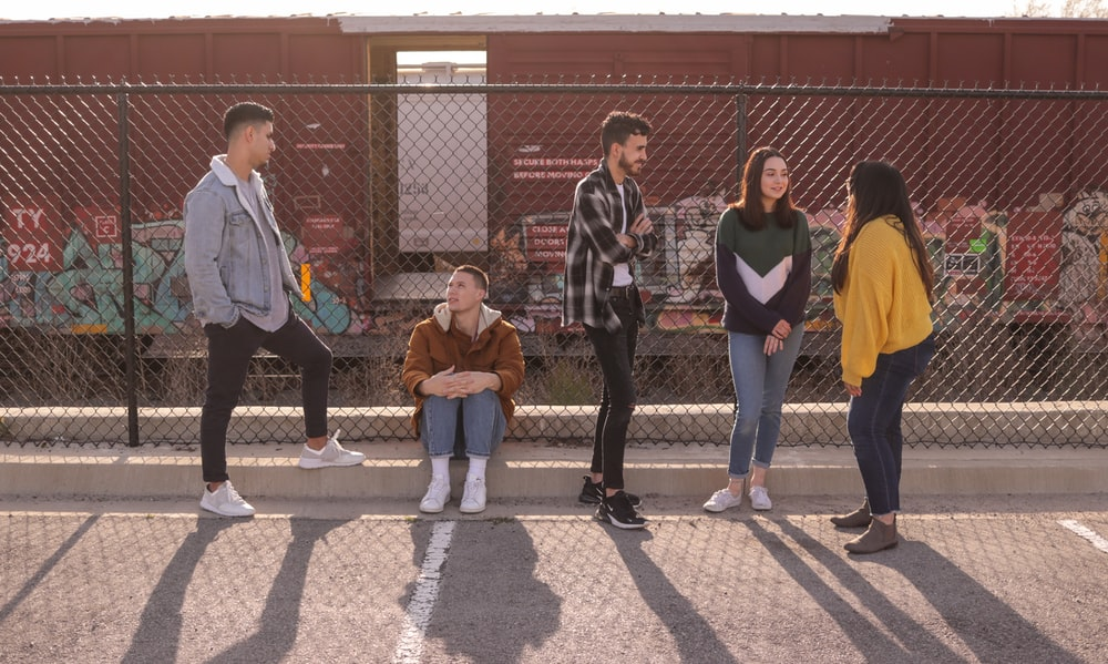 five persons on front of chain link fence