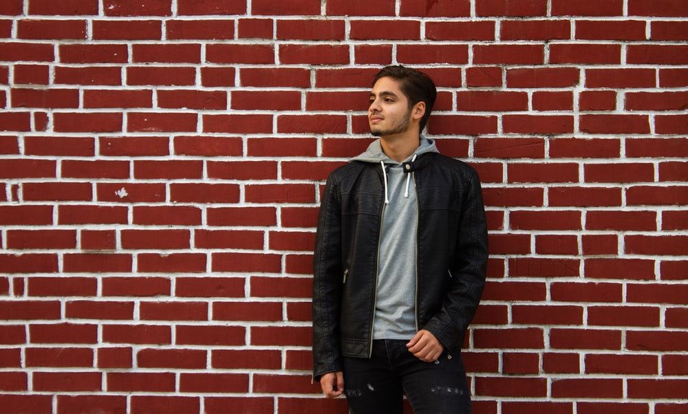 man in blue zip up jacket standing beside brown brick wall