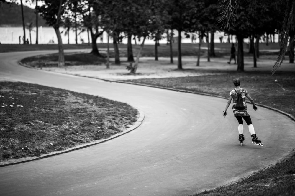 grayscale photography of girl in inline skates on road