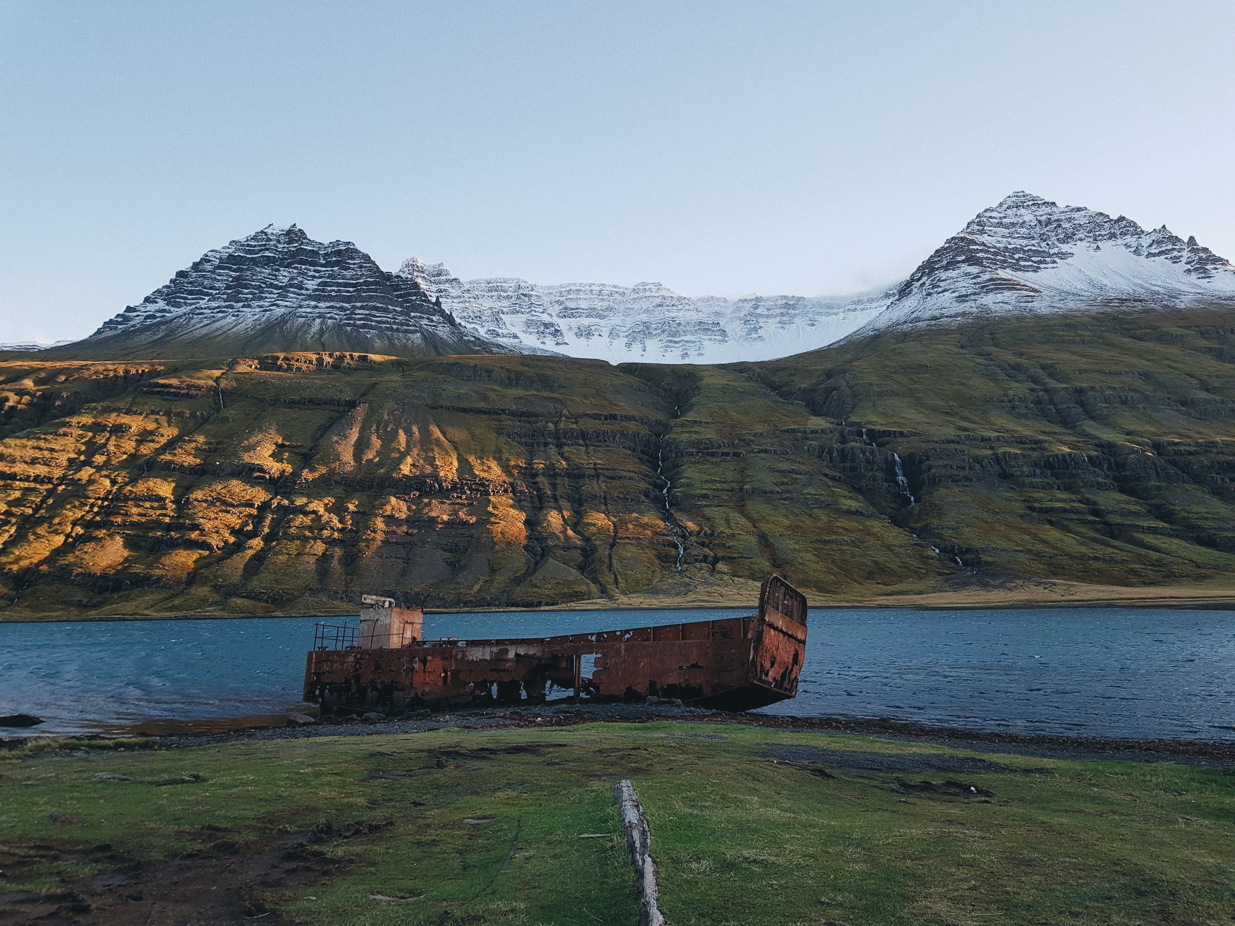wrecked red ship near body of water during daytime