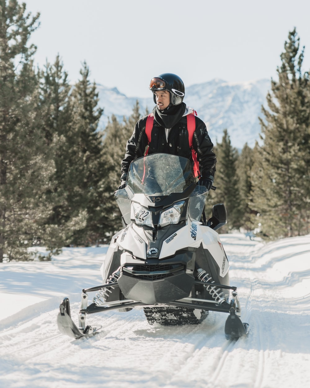 man in black winter jacket driving white snowmobile on snow-covered ground during daytime