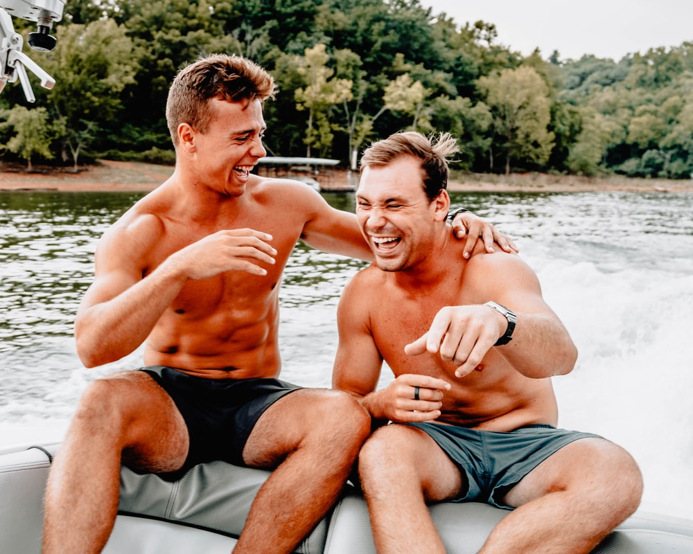 two men sitting on boat while laughing