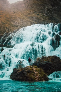 man standing on rock in front of waterfall