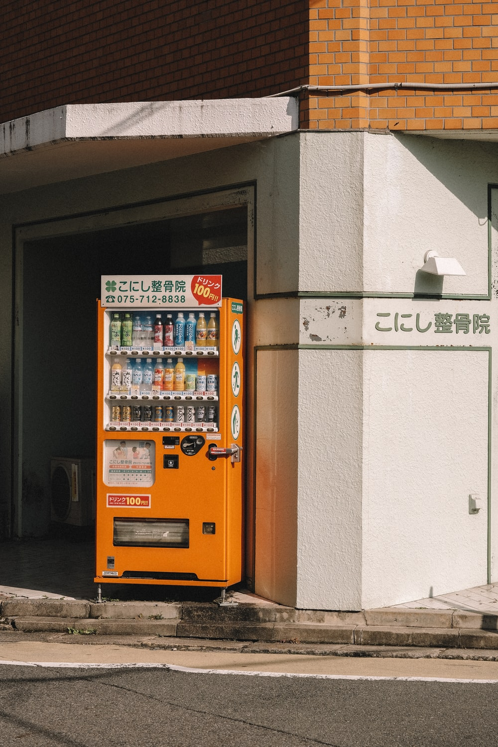 orange vending machine near building