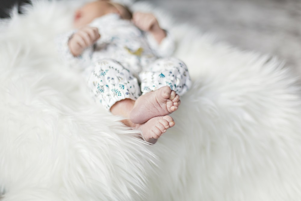selective focus photography of baby lying on fur bed