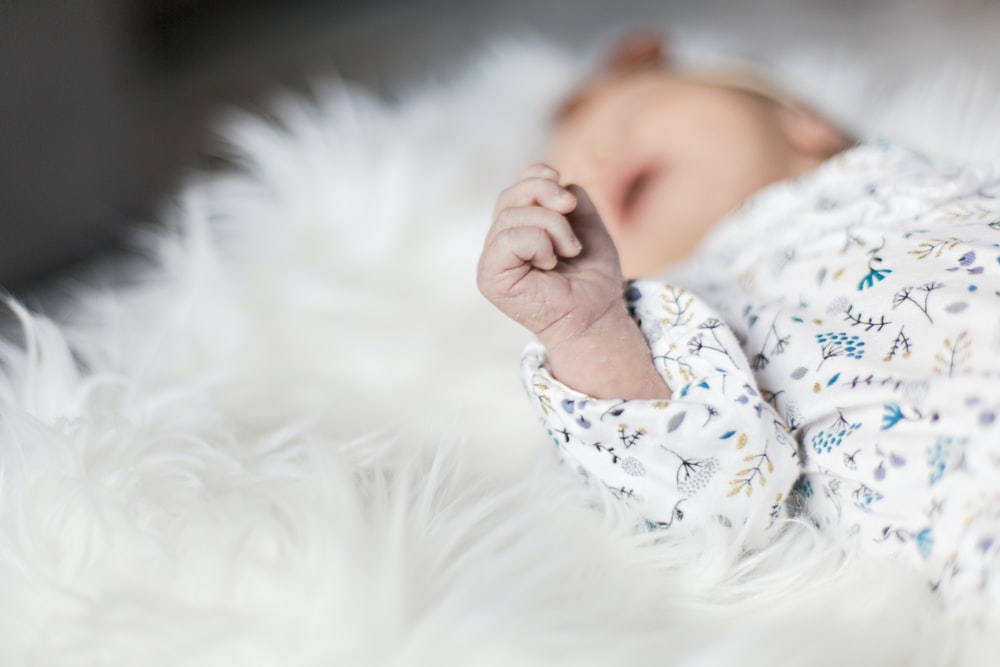 selective focus photography of baby sleeping on white fur pad