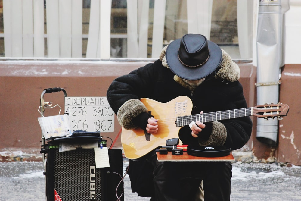 man playing with guitar near building