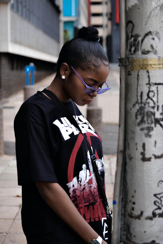 woman wearing black t-shirt standing near concrete post