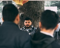 selective focus photography of man in gray and white plaid scarf leaning on tree during daytime