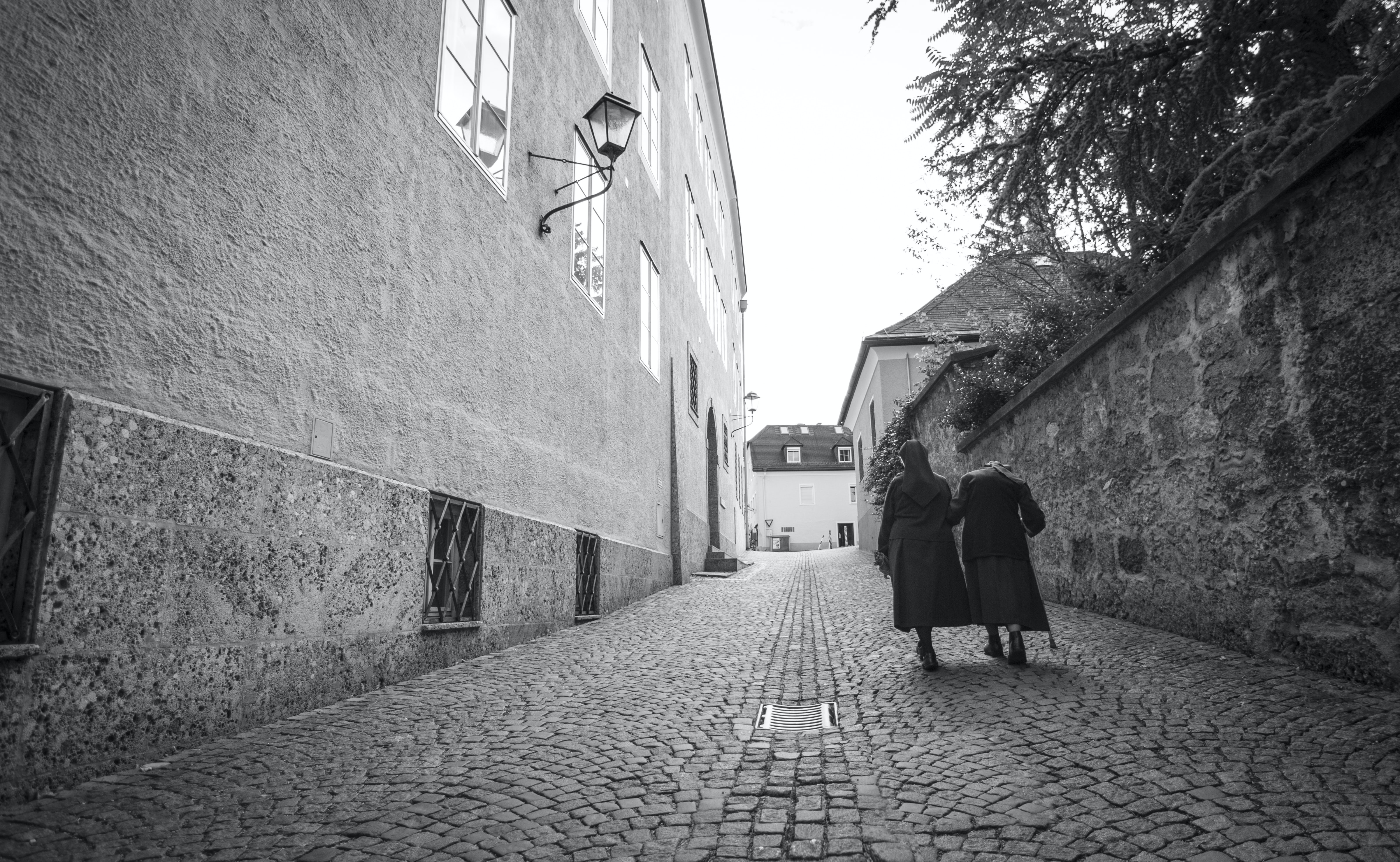 grayscale photo of two persons walking upward
