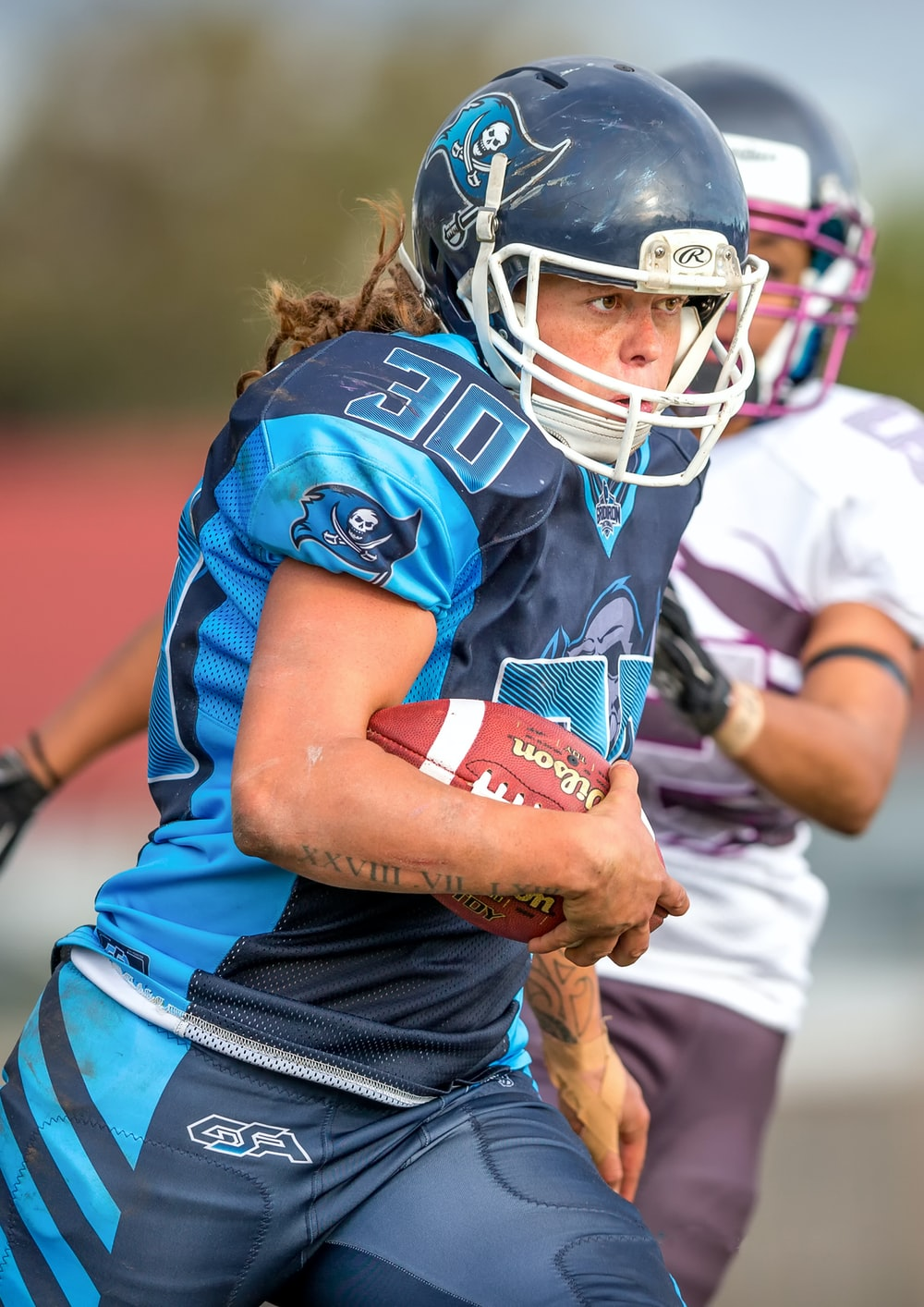 selective focus photography of woman in blue 30 jersey shirt holding brown football