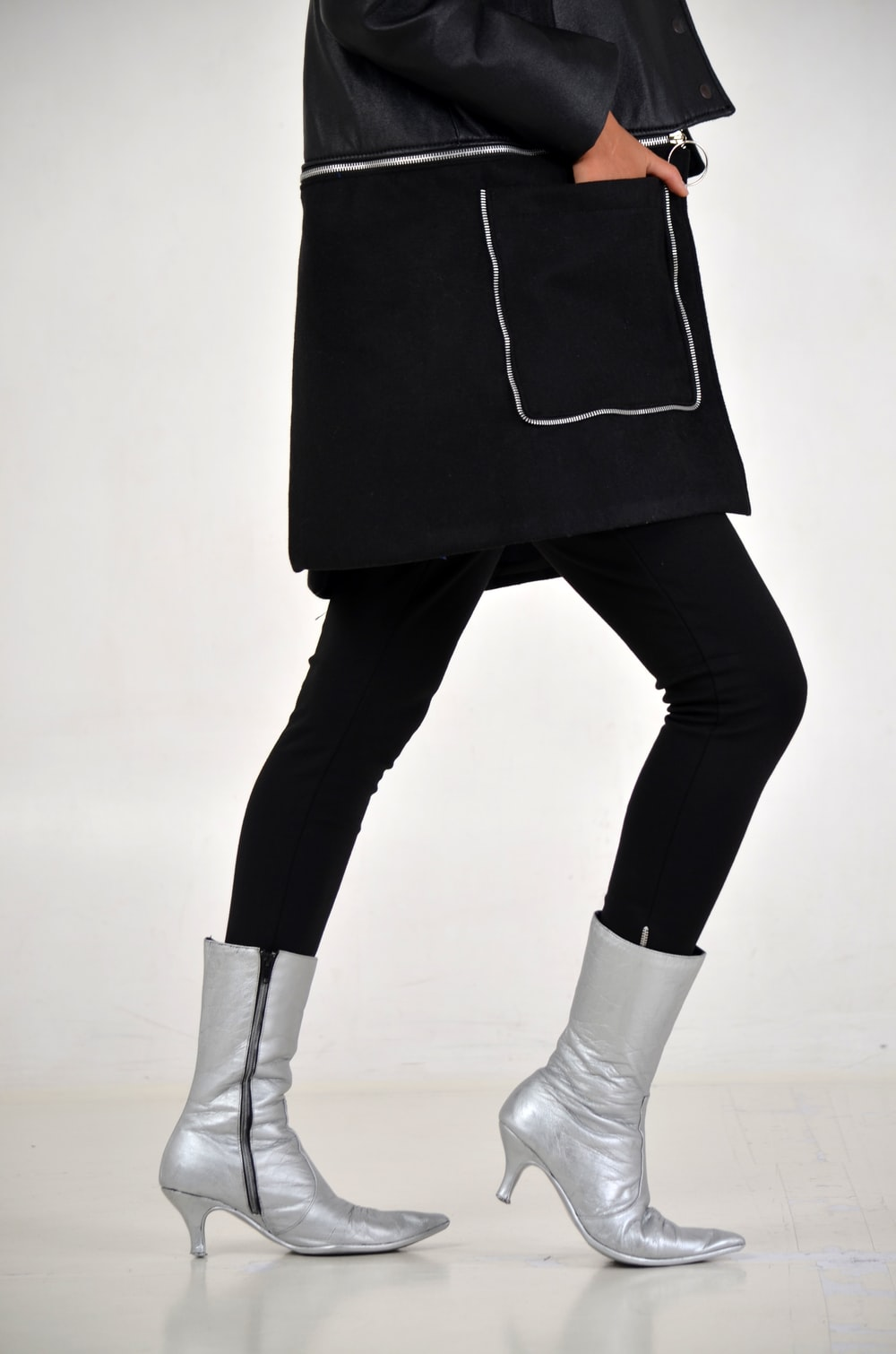 woman in black bottoms and silver side-zip boots