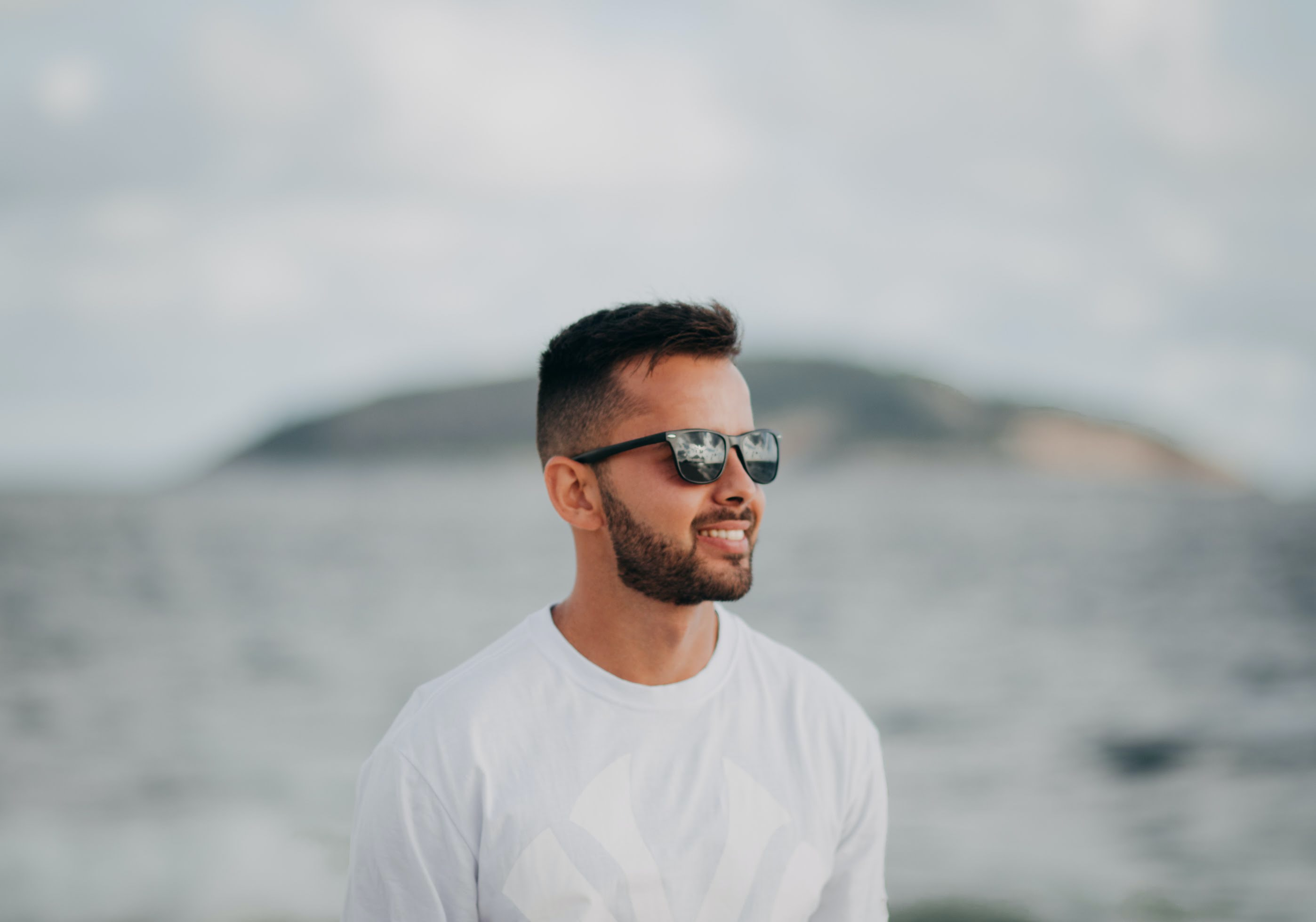 selective focus photography of smiling man in white crew-neck New York Yankers shirt and black sunglasses