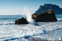 wave of water splashed on rock