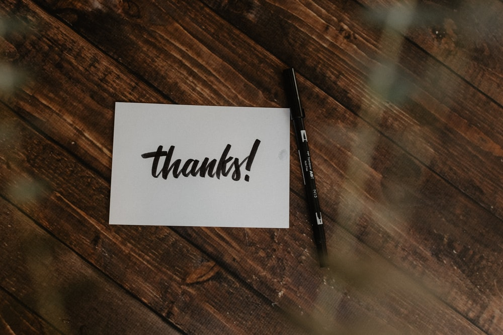 thanks! paper and black pen on wood surface