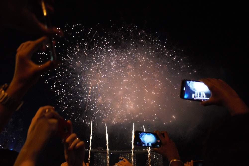 people taking photo of fireworks