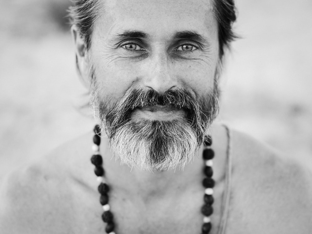 man in beads necklace grayscale photography
