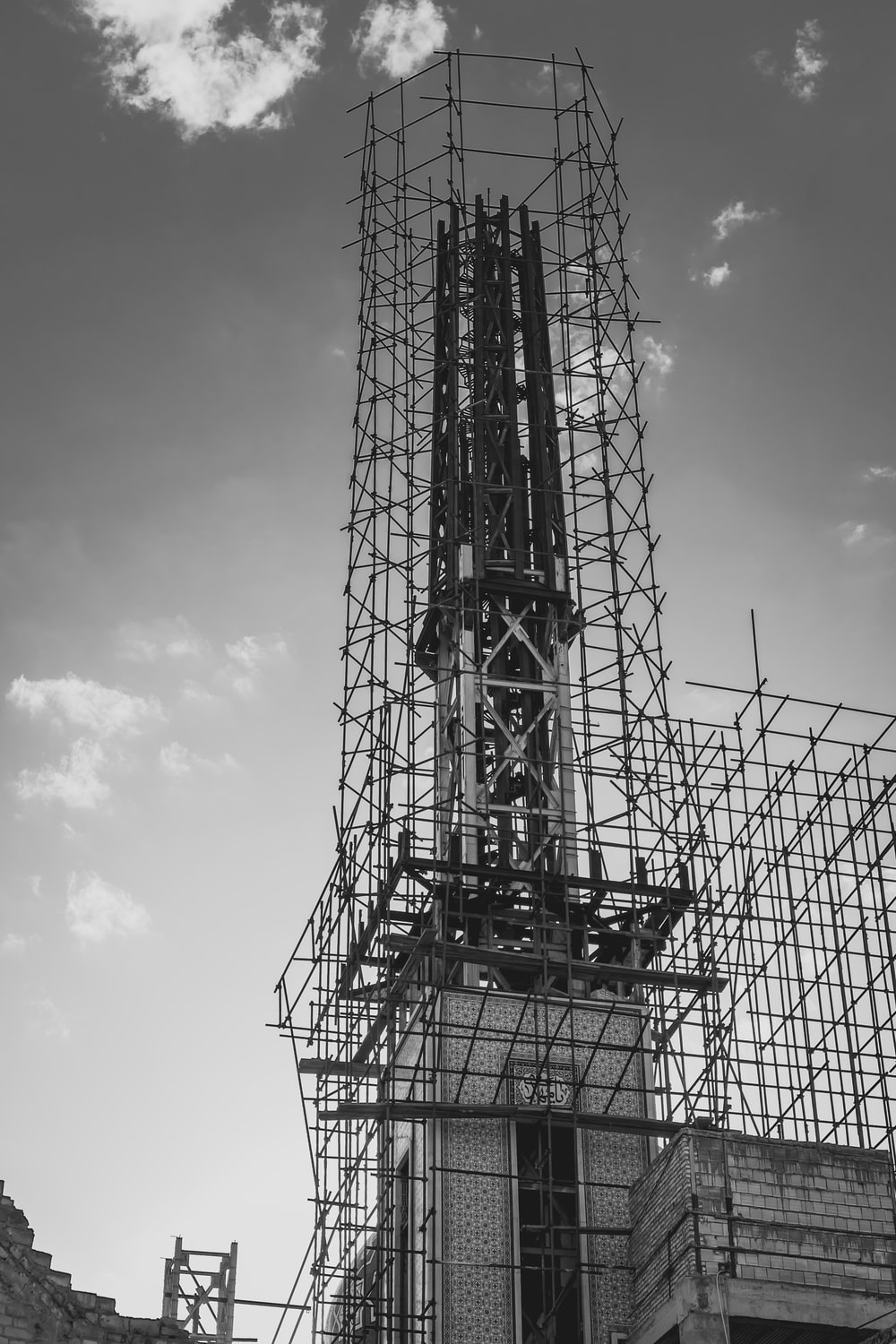 grayscale photography of scaffolding surrounding building
